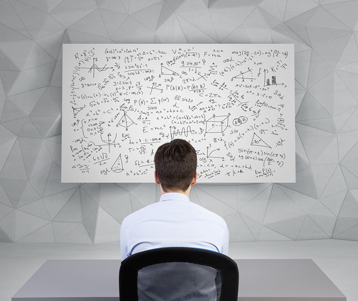 student man looking to desk with athematics equations and formulas